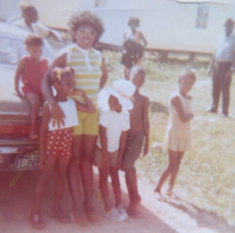 Old color photo of several African American children in front of a car with what appears to be their mother.