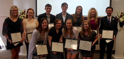 Undergraduate peer mentors receiving recognition plaques for their work.