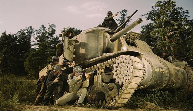 soldiers taking cover behind a tank