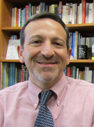 Headshot photo of Joshua Rothman in front of a bookcase. He is wearing a mauve shirt and tie.
