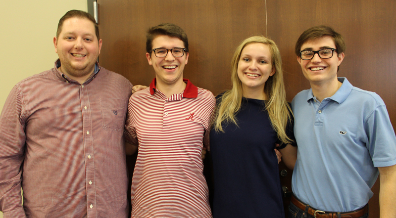 four history majors who are members of mock trial standing arm in arm.