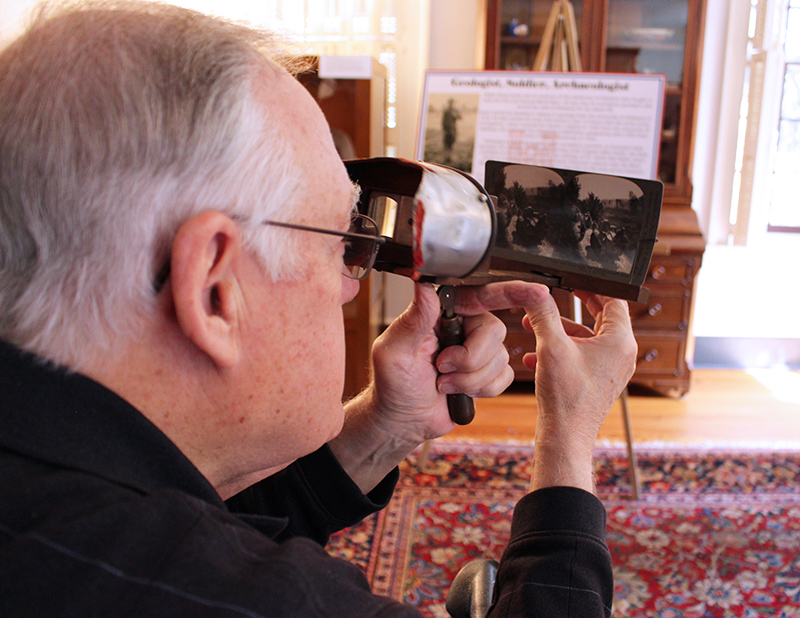 researcher viewing an old photo through a magnifying glass