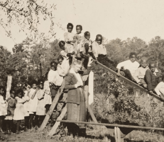 Black and white image of African-American children on a slide with a white teacher from a Lincoln school in Alabama