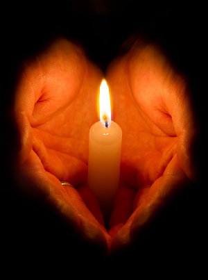 Two hands holding a lit candle.
