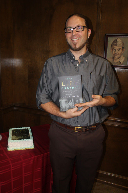Photograph of Dr. Peterson poses with his book in hand.