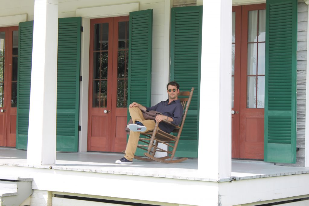 This is an image showing Noah Wylie sitting on a porch.