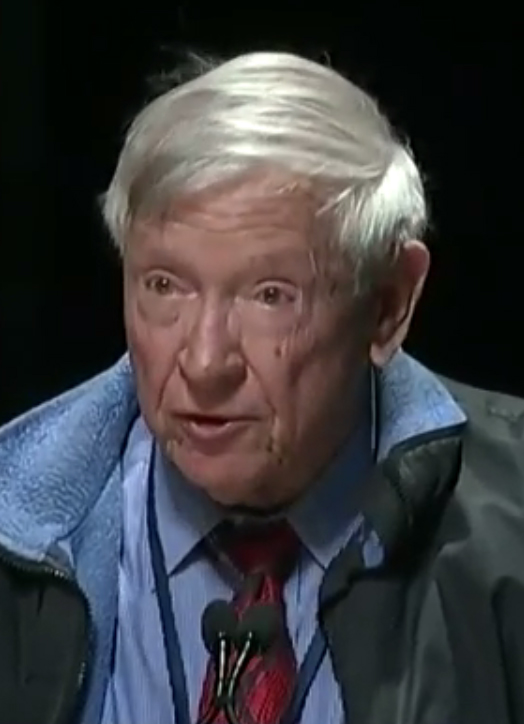 This image shows Dr. William C. Harris, wearing a tie and a jacket, speaking at Ford's Theater in Washington, DC