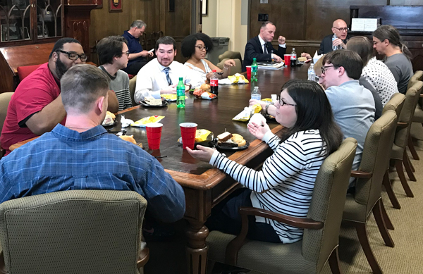 Graduate students and guest eat lunch.